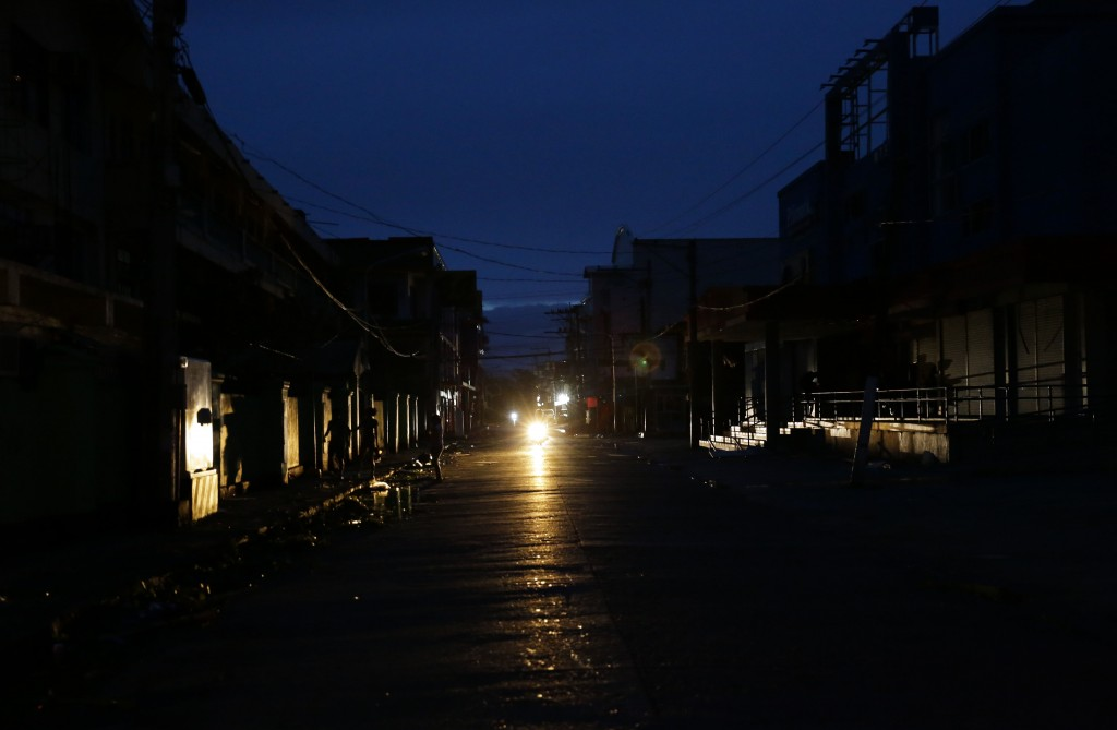 A motorcycle provides light along a dark street after electricity was shut-off following the onslaught of Typhoon Mangkhut in Tuguegarao city in Cagay