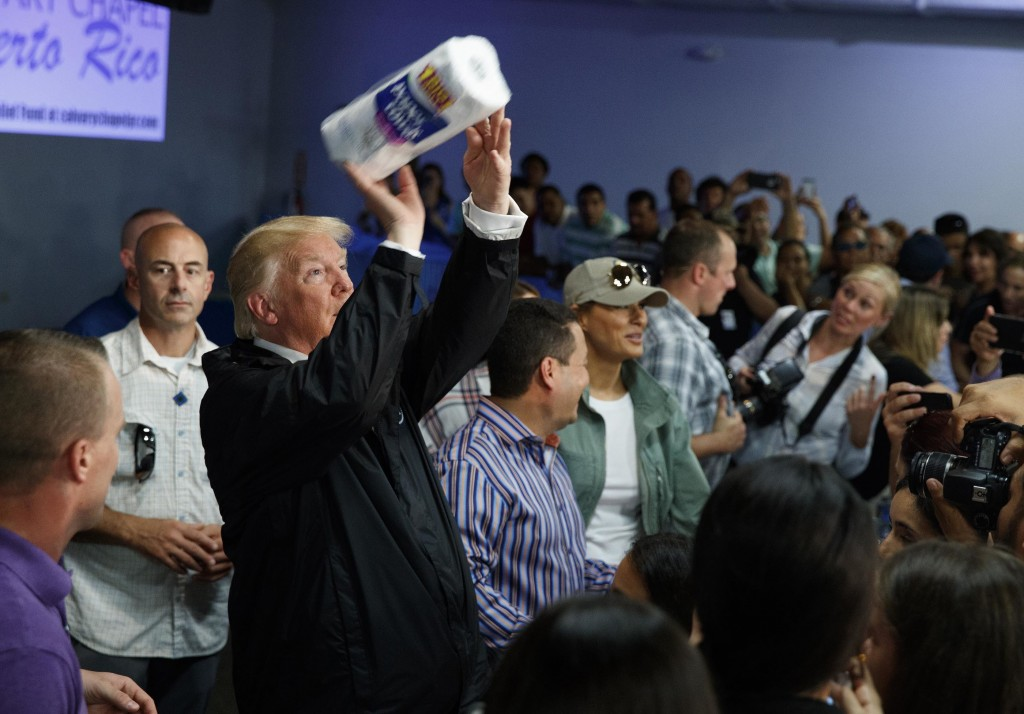 FILE - In this Oct. 3, 2017 file photo, President Donald Trump tosses paper towels into a crowd at Calvary Chapel in Guaynabo, Puerto Rico.  (AP Photo