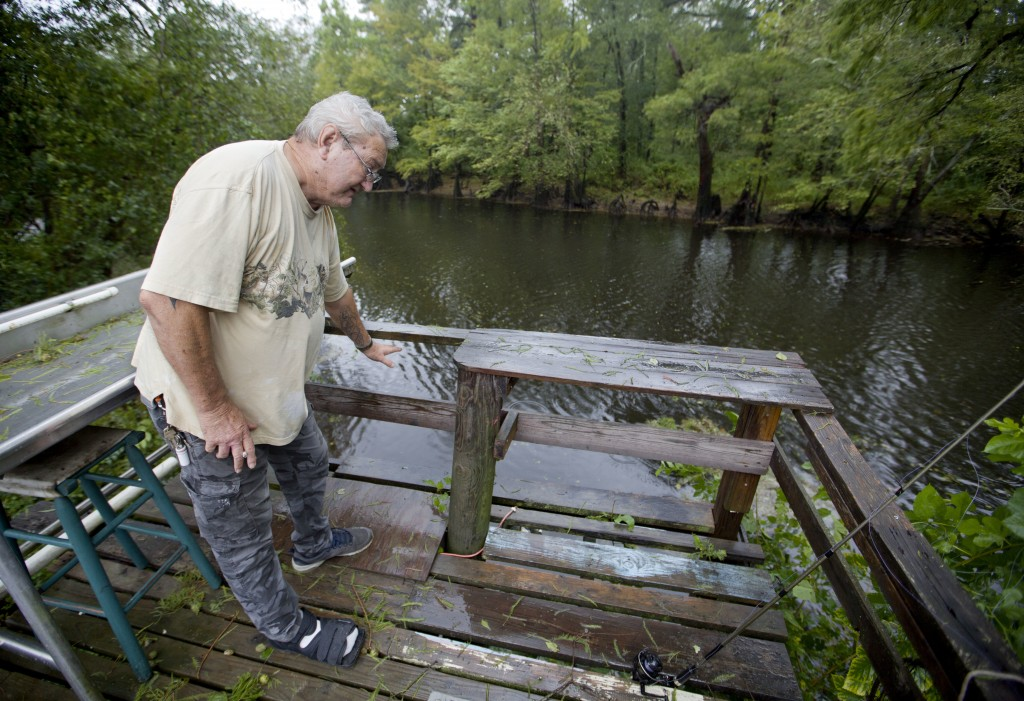 Bennie Todd shows how high the Lumber River rose during Hurricane Matthew two years in his backyard in Lumberton, N.C., Friday, Sept. 14, 2018. Now th