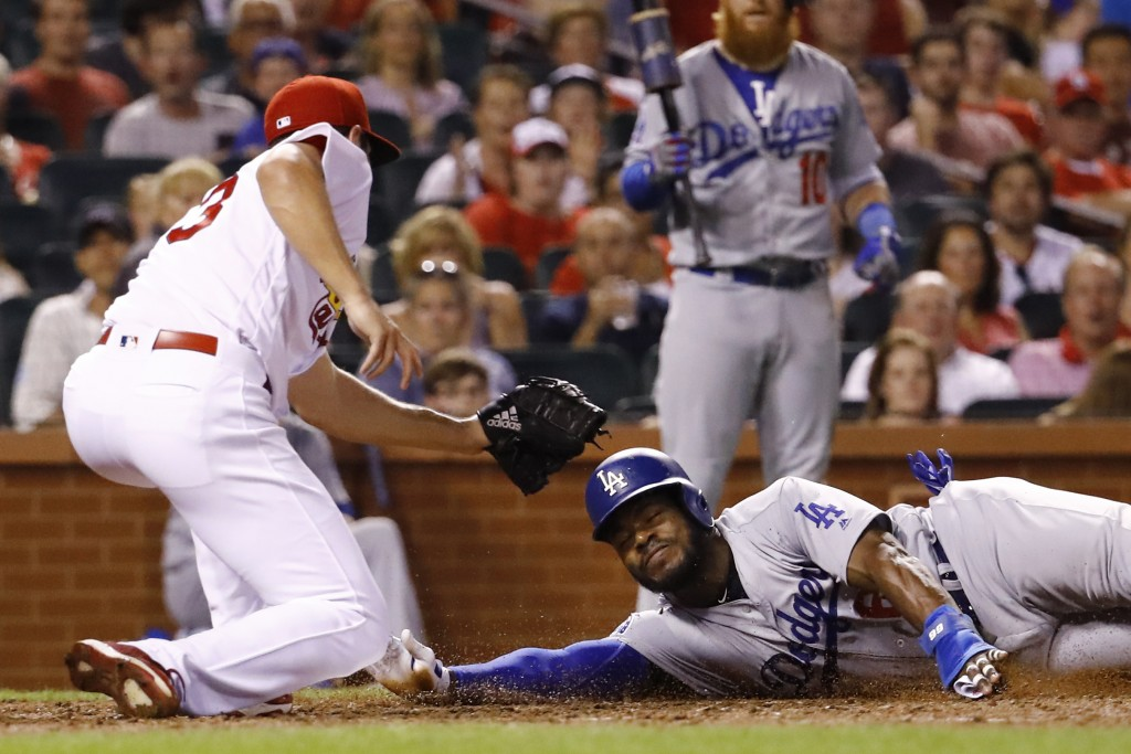 Los Angeles Dodgers' Yasiel Puig, right, is tagged out at the plate by St. Louis Cardinals relief pitcher Dakota Hudson, while attempting to score on