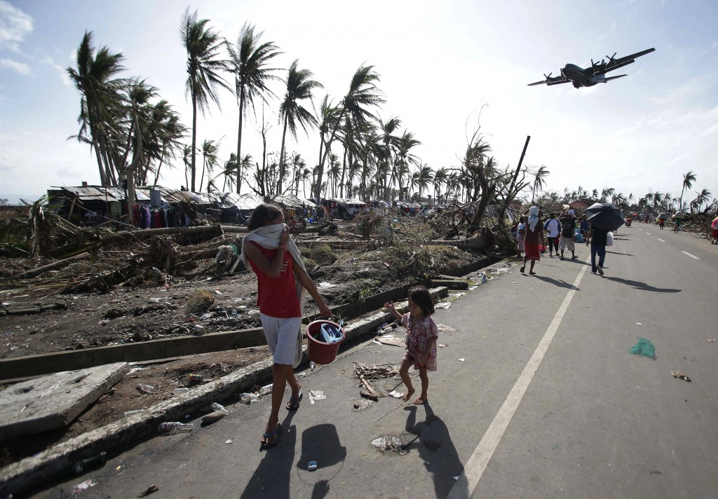 FILE- In this Nov. 11, 2013, file photo, survivors look as a military C-130 plane arrives at typhoon-ravaged Tacloban city, Leyte province central Phi