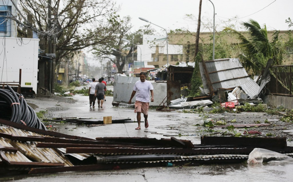 FILE - In this Saturday, Sept. 15, 2018, file photo, a resident walks beside toppled structures as Typhoon Mangkhut barreled across Tuguegarao city in