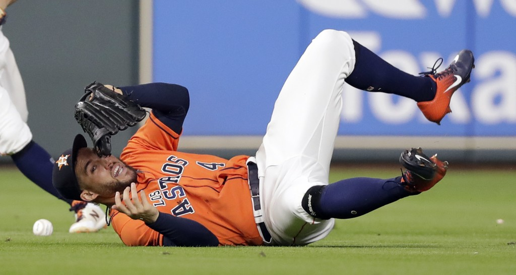 Houston Astros center fielder George Springer (4) tumbles while trying to catch a single by Arizona Diamondbacks' A.J. Pollock during the eighth innin...
