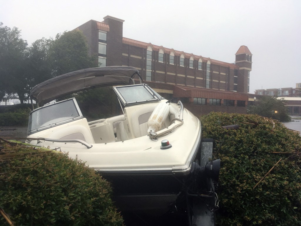 A speed boat sits wedged in bushes in the parking lot of a waterfront hotel in New Bern, N.C., on Friday, Sept. 14, 2018. Winds and rains from Hurrica