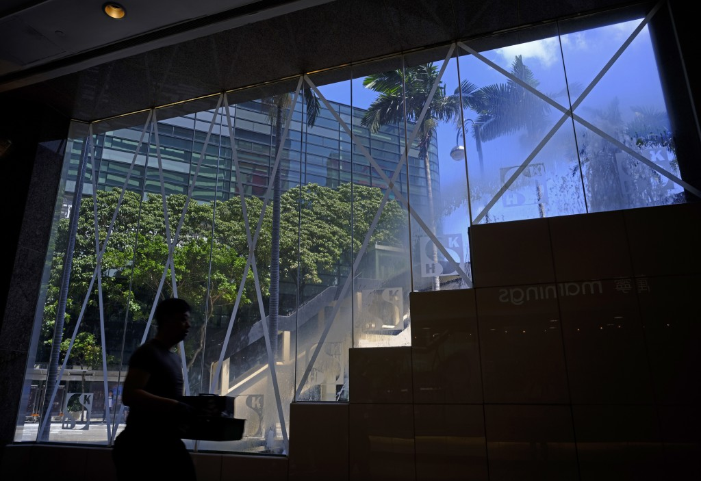 A man walks past windows taped in preparation for approaching typhoon Mangkhut in Hong Kong Saturday, Sept. 15, 2018. Typhoon Mangkhut slammed into th