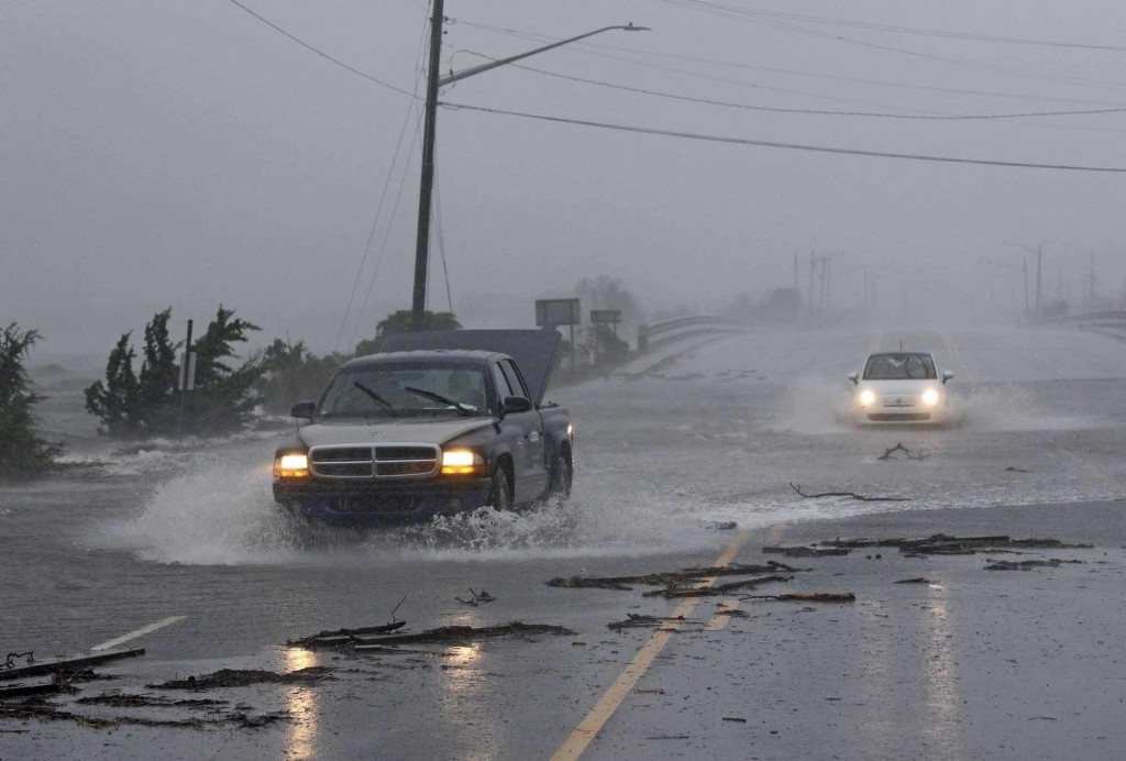 Vehicles drive through water from the White Oak River flooding Highway 24 as Hurricane Florence hit Swansboro N.C., Friday, Sept. 14, 2018. (AP Photo/