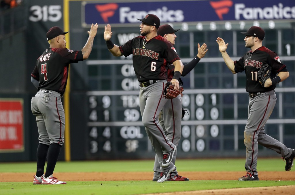 Arizona Diamondbacks' Ketel Marte (4), David Peralta (6), Nick Ahmed and A.J. Pollock (11) celebrate after a baseball game against the Houston Astros