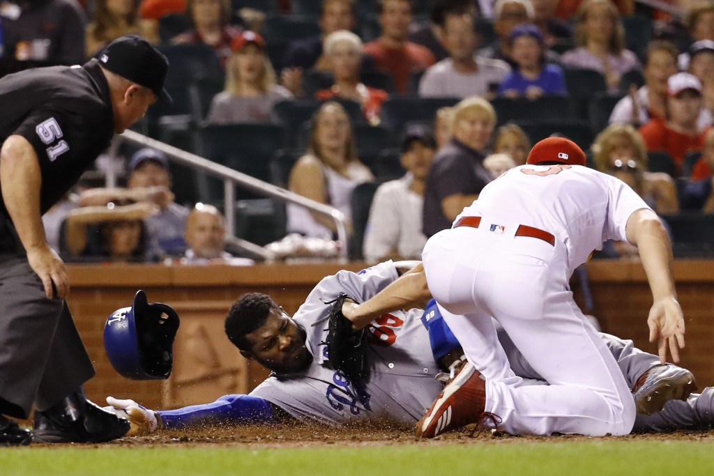 Los Angeles Dodgers' Yasiel Puig, center, is tagged out at the plate by St. Louis Cardinals relief pitcher Dakota Hudson, as he attempted to score on