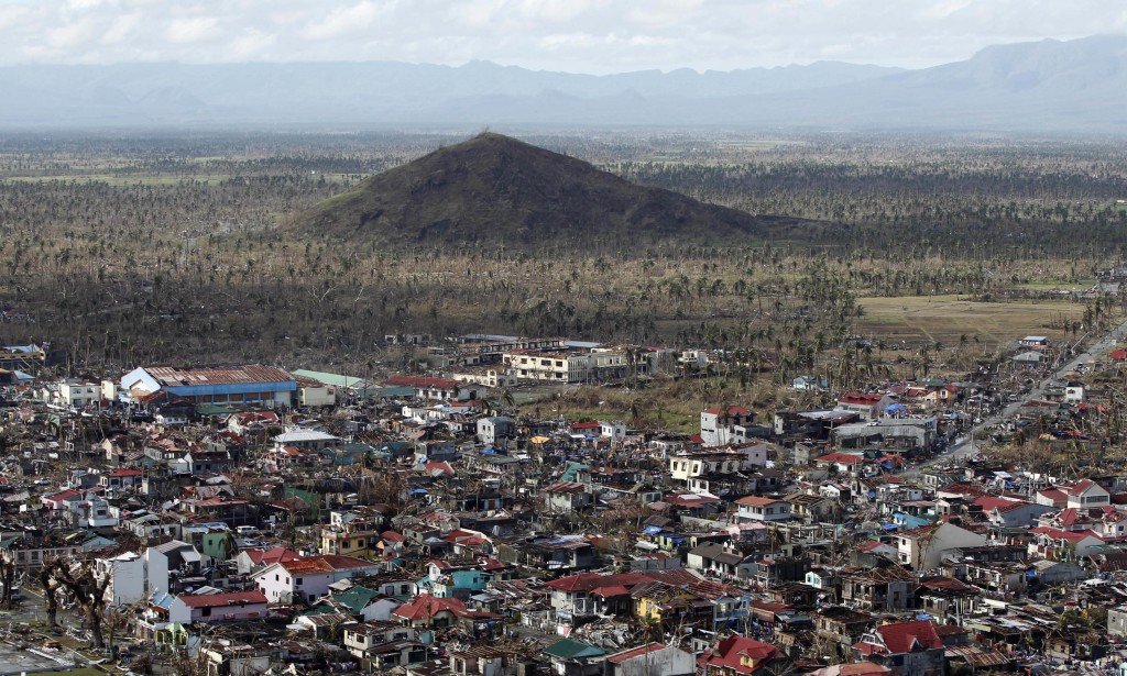 FILE- In this Nov. 13, 2013, file photo, an aerial view shows the destruction left from Typhoon Haiyan in the coastal town of Tanawan, central Philipp