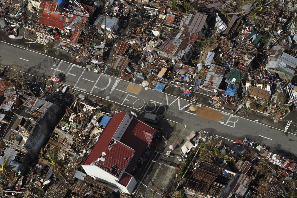 FILE - In this Nov. 13, 2013, file photo, an aerial view shows signs for help and food amid the destruction left from Typhoon Haiyan in the coastal to...