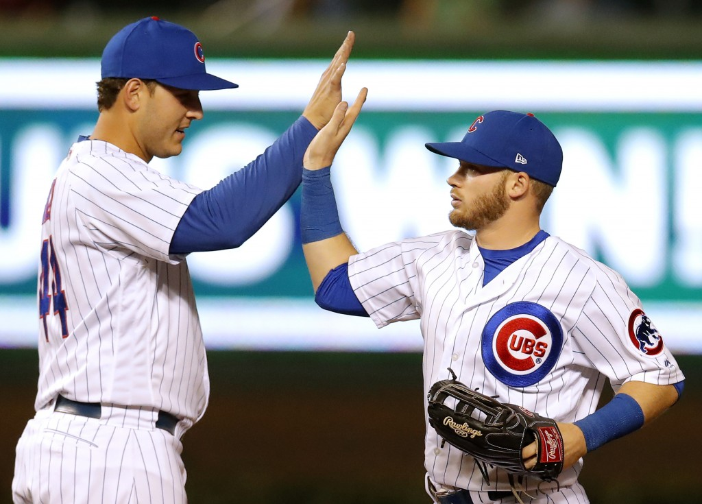 Chicago Cubs' Anthony Rizzo, left, and Ian Happ celebrate their win over the Cincinnati Reds at the end of a baseball game Friday, Sept. 14, 2018, in