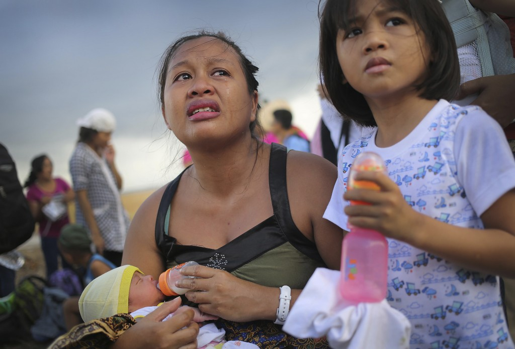 FILE- In this Nov. 14, 2013, file photo, a woman cries as she pleads with military to let her husband through to the front of the queue as they wait f...