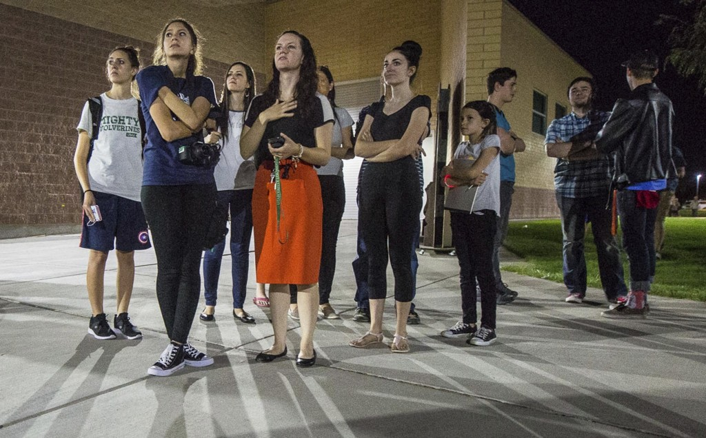 In this Thursday, Sept. 13, 2018, photo, residents watch a wildfire burning from outside Salem Hills High School in Salem, Utah.  in Salem, Utah. (Qil