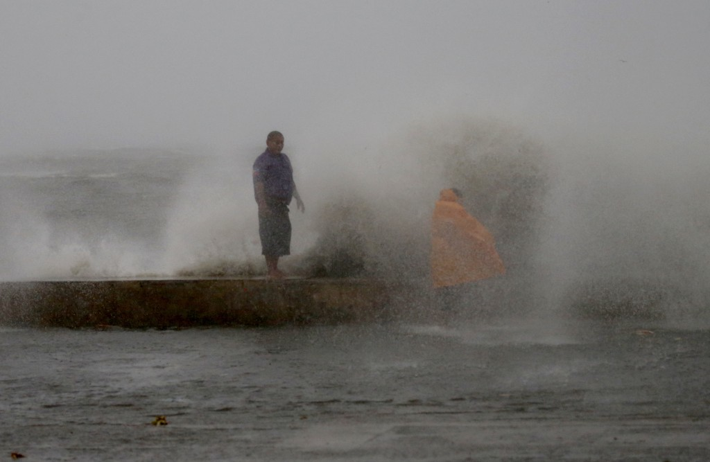 Waves slam the seawall as Typhoon Mangkhut continues to batter the country after hitting land in northeastern Philippines before dawn Saturday, Sept.
