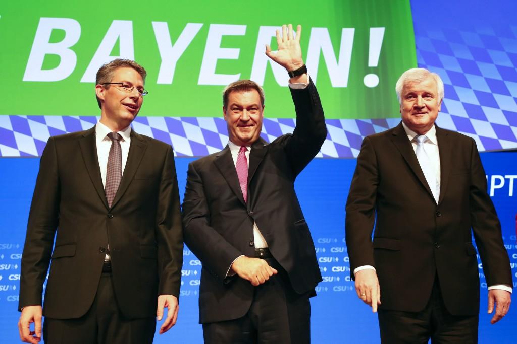 Bavarian State Governor Markus Soeder, center, waves as he arrives besides German Interior Minister Horst Seehofer, right, and Secretary General Marku