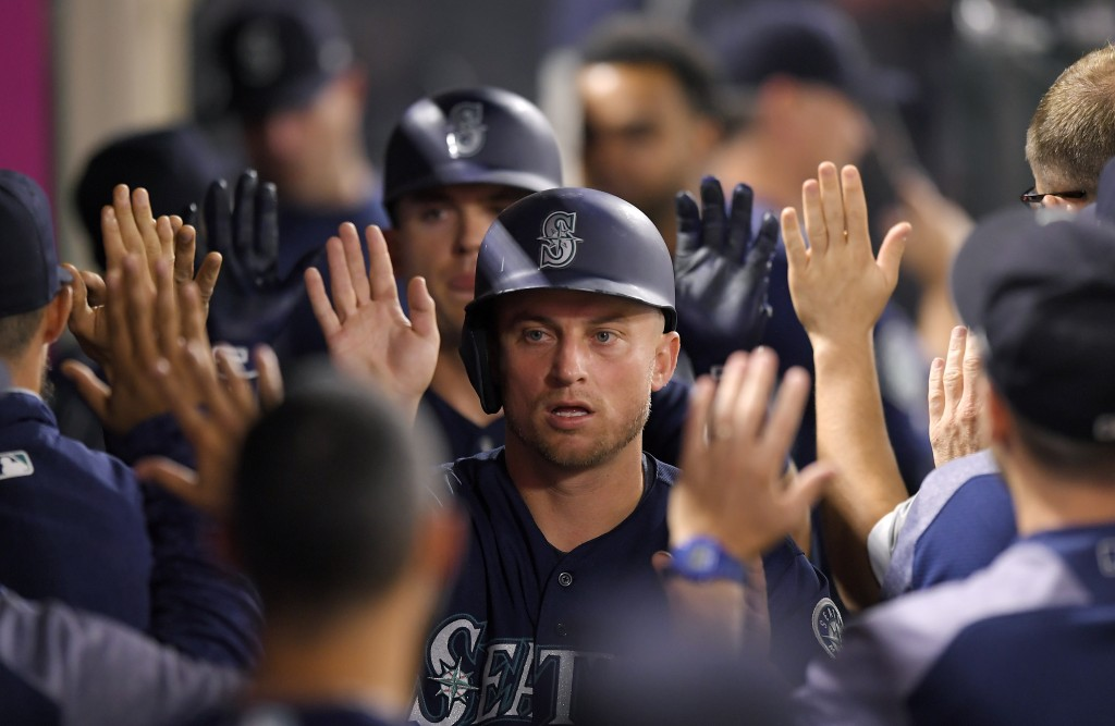 Seattle Mariners' Kyle Seager is congratulated by teammates in the dugout after scoring on a single by Dee Gordon during the seventh inning of a baseb