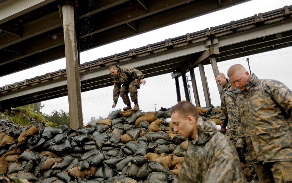 Members of the North Carolina National Guard finish stacking sand bags under a highway overpass near the Lumber River which is expected to flood from