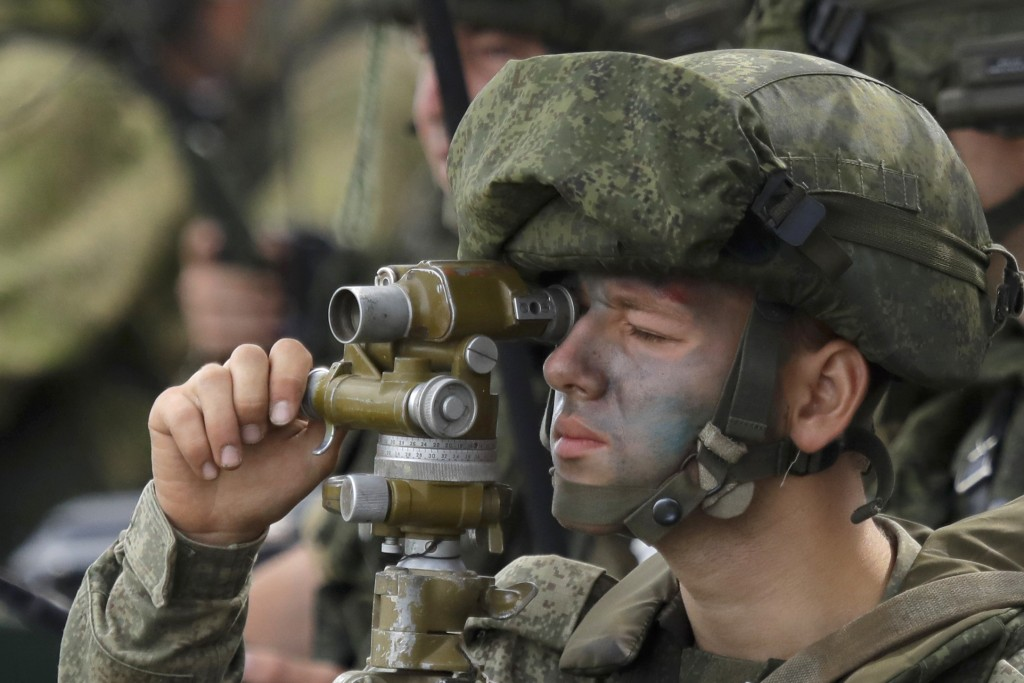 """A Russian officer watches through a rear sight during Russian military maneuvers Vostok 2018 on the training ground """"Klerk,"""" about 50 kilometers (31 m"""
