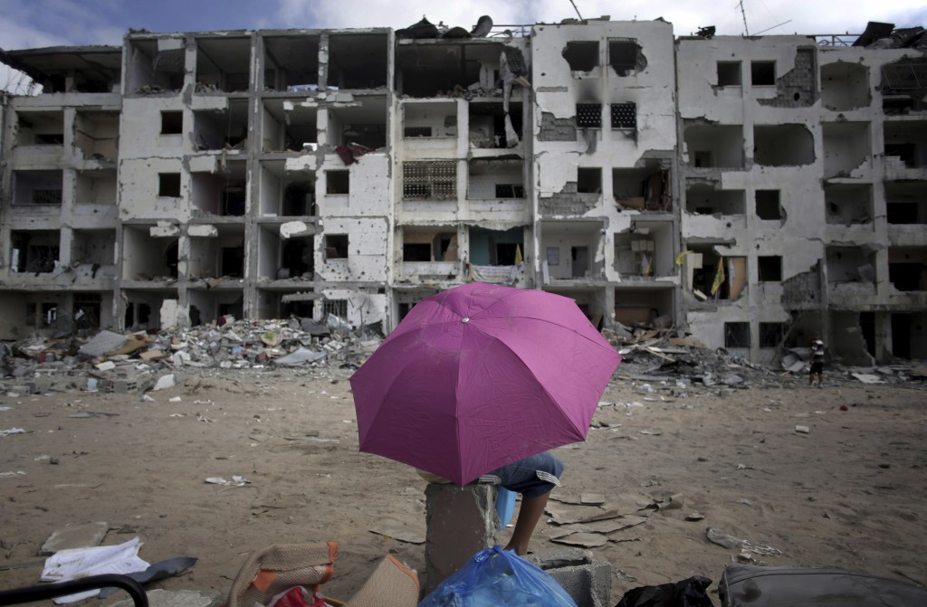 FILE - In this Aug. 11, 2014 file photo, a Palestinian boy holds an umbrella as he rests in front of the damaged Nada Towers residential neighborhood