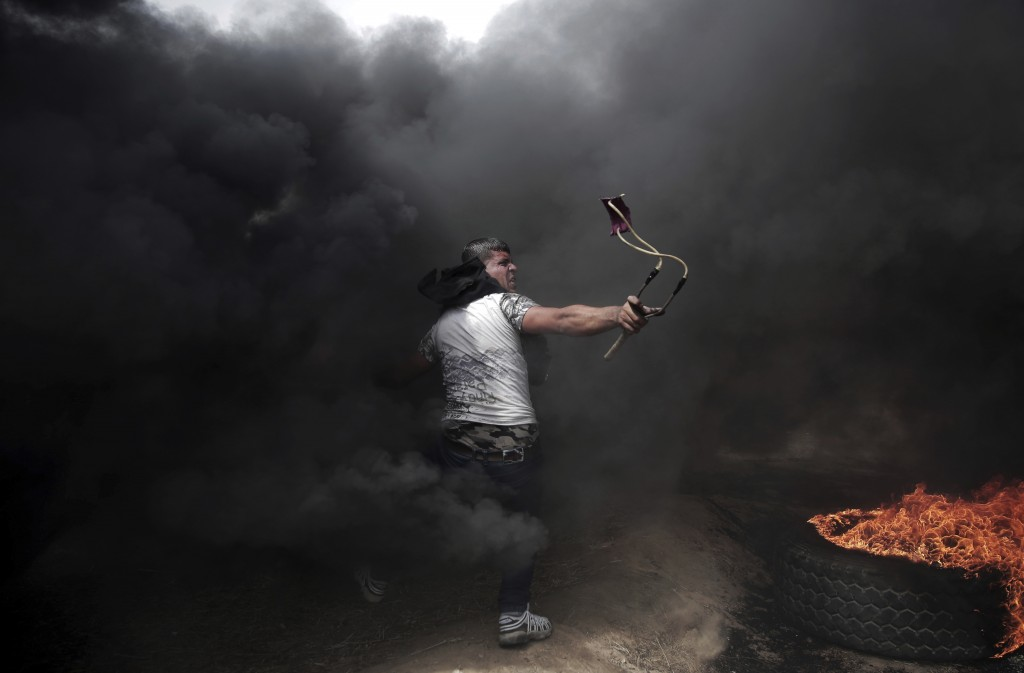 FILE - In this April 20, 2018 file photo, a Palestinian protester hurls stones at Israeli troops during a protest at the Gaza Strip's border with Isra