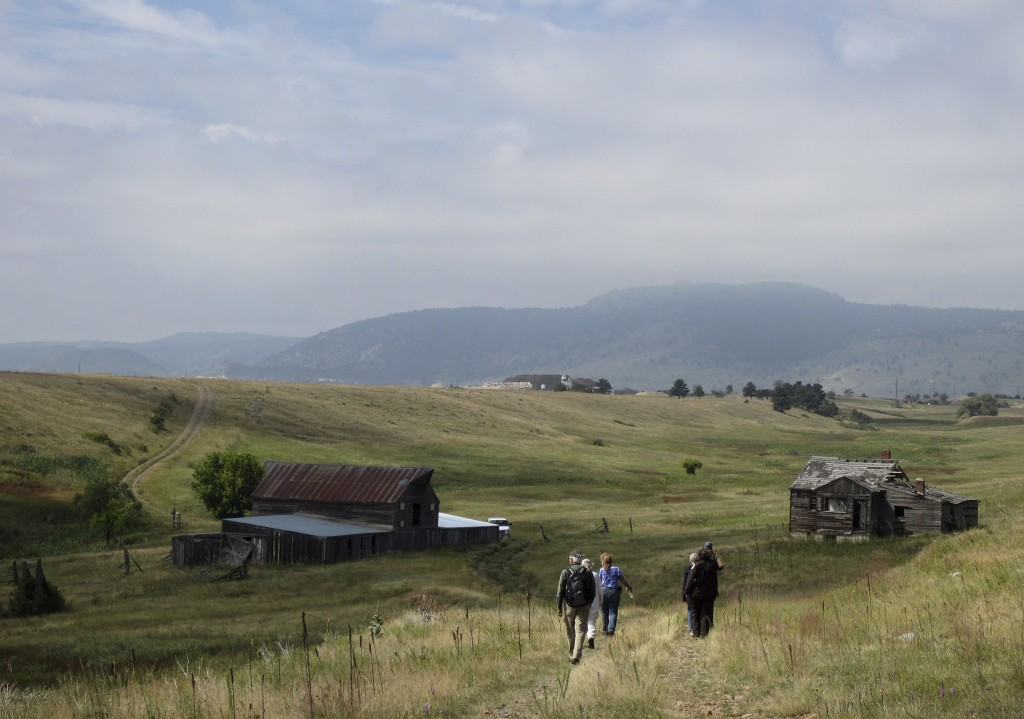 FILE - In this Aug. 11, 2017 file photo, visitors approach a former ranch house and barn during a guided hike on the Rocky Flats National Wildlife Ref