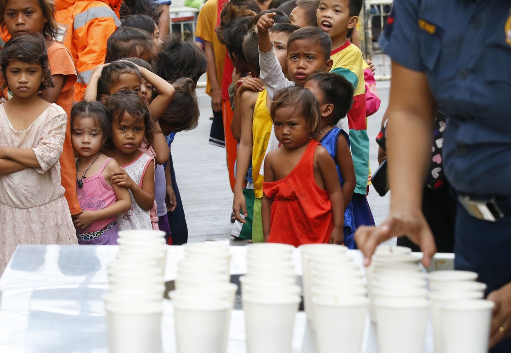 FILE - In this Saturday, Sept. 15, 2018, file photo, residents living along the coastal community of Baseco wait to receive rice porridge as they seek...