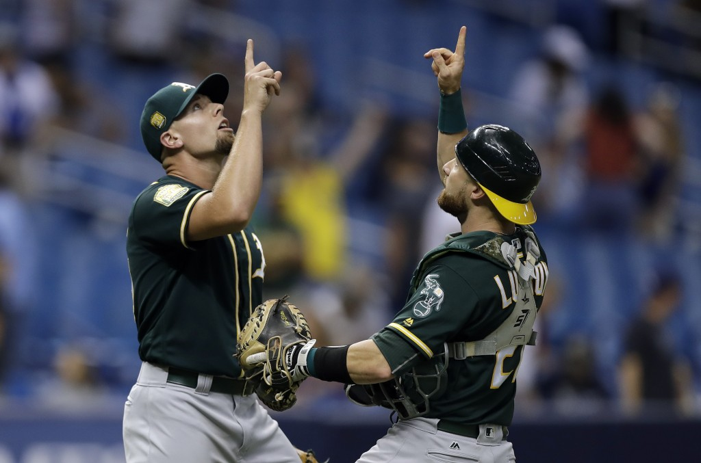 Oakland Athletics pitcher Blake Treinen, left, celebrates with catcher Jonathan Lucroy after defeating the Tampa Bay Rays 2-1 during a baseball game F