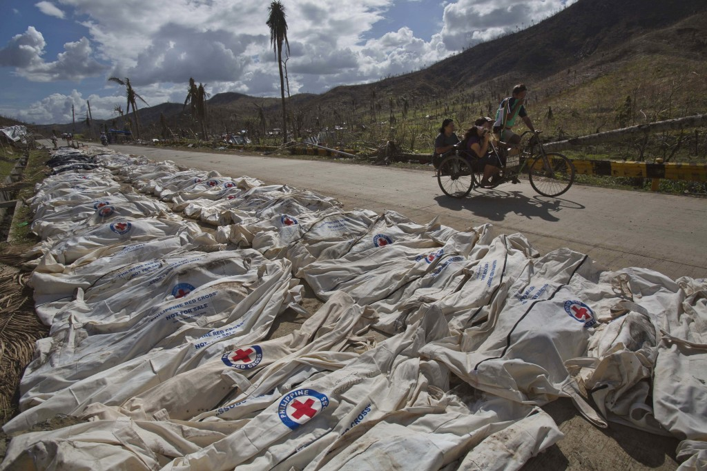 FILE- In this Nov. 19, 2013, file photo, Typhoon Haiyan survivors pass by hundreds of victims lying in body bags on the roadside until forensic expert