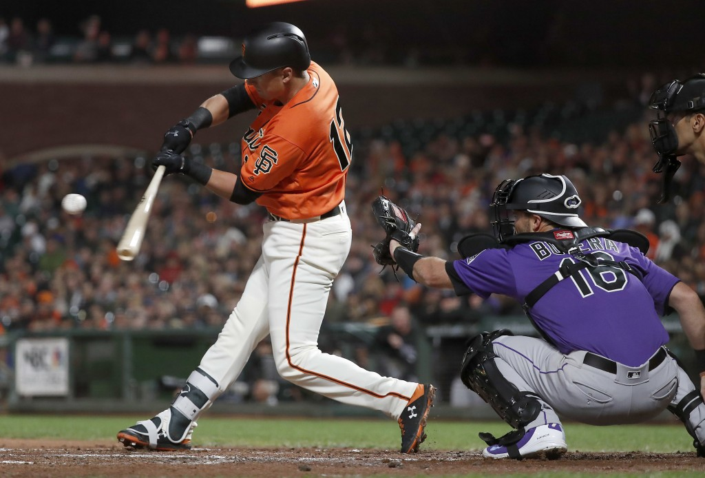 San Francisco Giants' Joe Panik (12) hits a single against the Colorado Rockies during the second inning of a baseball game in San Francisco, Friday,