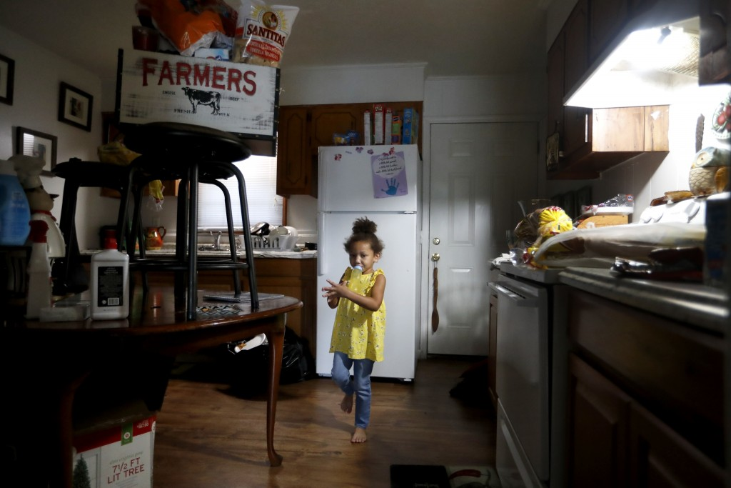 Ahblyssyn Lewis, 4, stands in the kitchen of her home as food and other items are placed high off the floor, in Lumberton, N.C., Friday, Sept. 14, 201