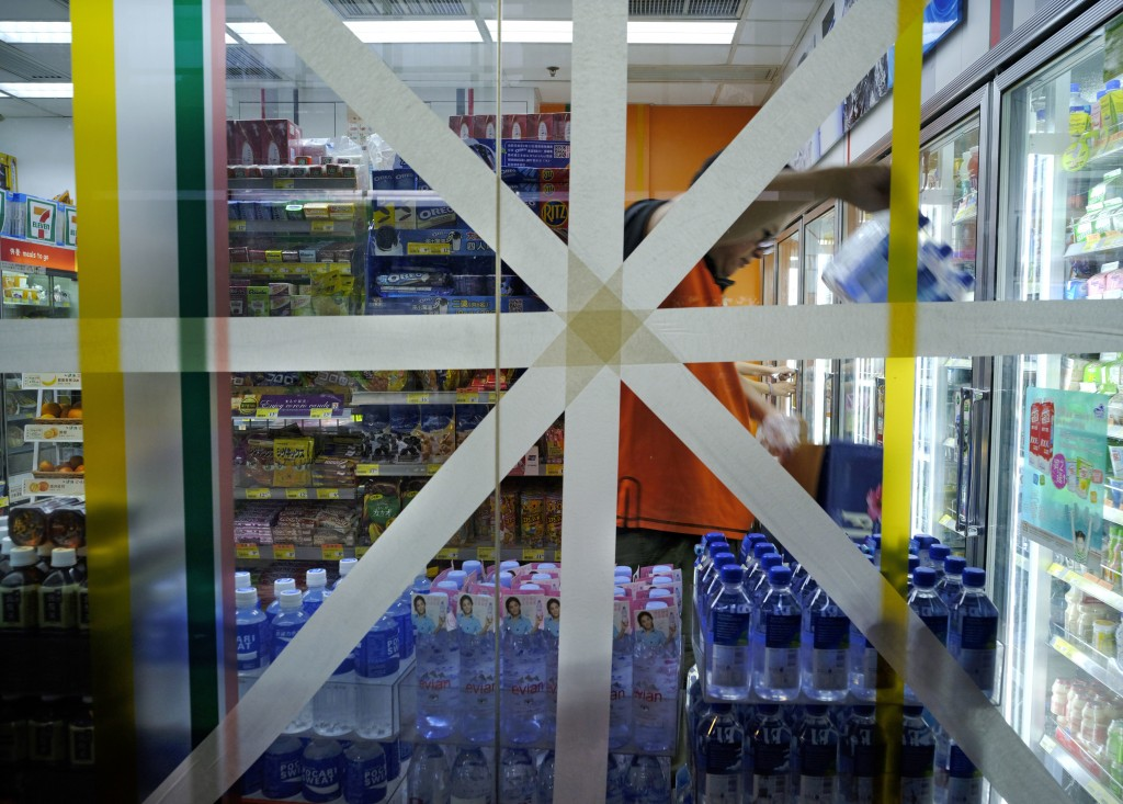 FILE - In this Saturday, Sept. 15, 2018, file photo, a convenience store glass wall is taped in preparation for approaching typhoon Mangkhut in Hong K...