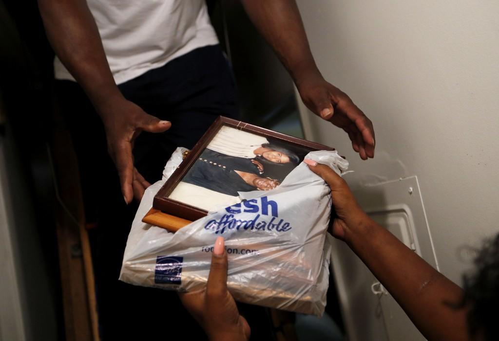 Nichole Worley passes family photos to her husband, Milton Johnson, as they pack belongings into the attic of their home in Lumberton, N.C., Friday, S