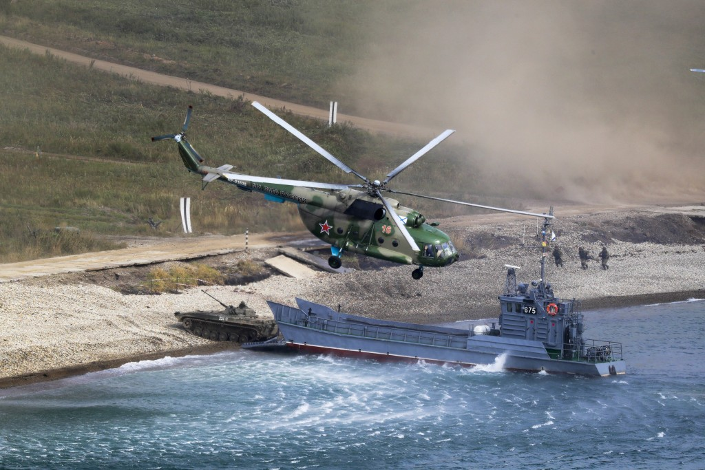 A Russian navy landing vessel unloads an armored vehicle as a military helicopter flies overhead during Russian military maneuvers Vostok 2018 on the