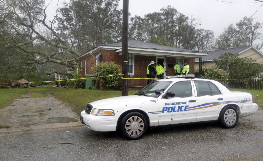 Police talk outside the home where a woman and her baby were killed by a fallen tree in Wilmington, N.C., after Hurricane Florence made landfall Frida