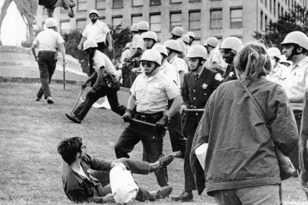 FILE - In this Aug. 26, 1968 file photo, Chicago police officers wielding nightsticks confront a demonstrator on the ground in Grant Park after protes