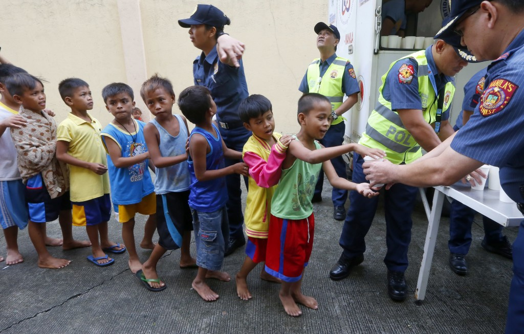 Manila police distribute rice porridge to residents living along the coastal community of Baseco as they evacuate during the onslaught of Typhoon Mang...