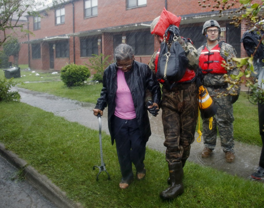 A rescue team from the North Carolina National Guard 1/120th battalion evacuates an elderly woman from her apartment as the rising floodwaters from Hu