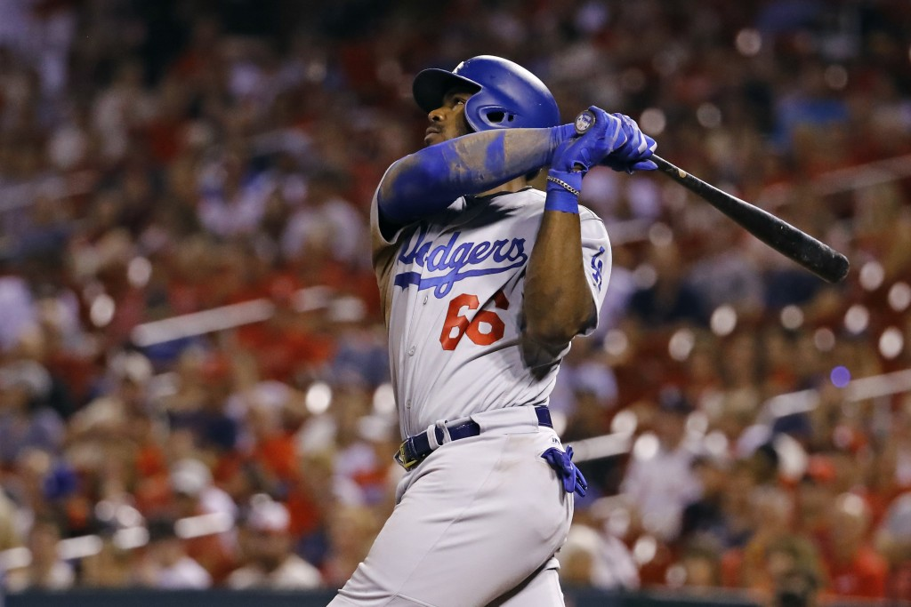 Los Angeles Dodgers' Yasiel Puig watches his second home run of the night leave the ballpark during the ninth inning of a baseball game against the St