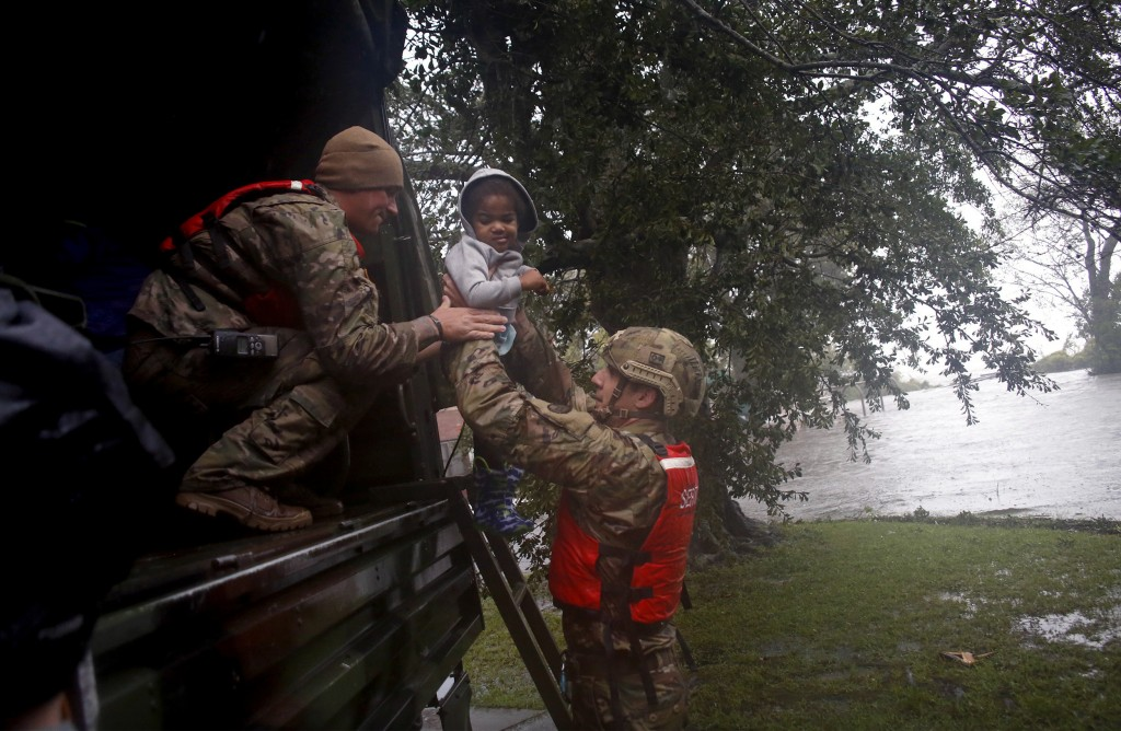 Rescue team members Sgt. Matt Locke, left, and Sgt. Nick Muhar, right, from the North Carolina National Guard 1/120th battalion, evacuates a family as