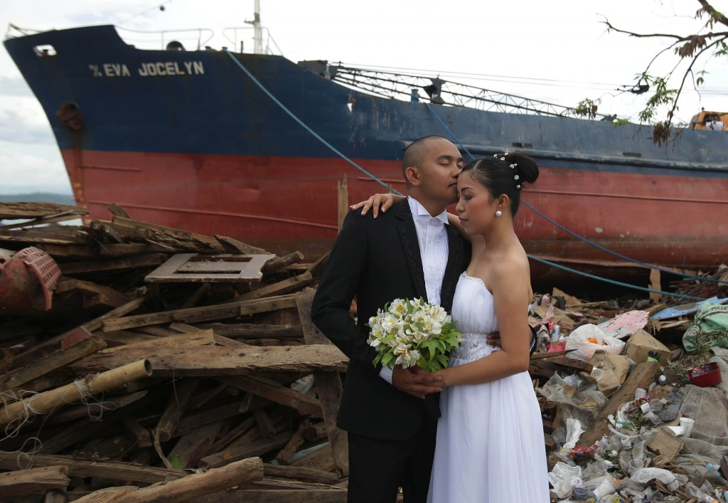 FILE- In this Dec. 7, 2013, file photo, Filipino groom Earvin Nierva, left, kisses his bride Riza as they pose for their wedding pictures taken by a p...