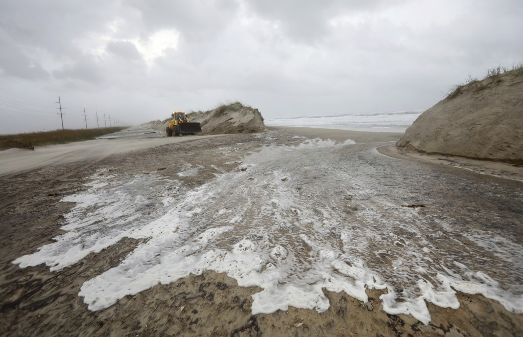 Water passes though a breach in the dune line on Hwy 12 between Frisco and Hatteras Village, N.C., Friday, Sept. 14, 2018. (Steve Earley /The Virginia