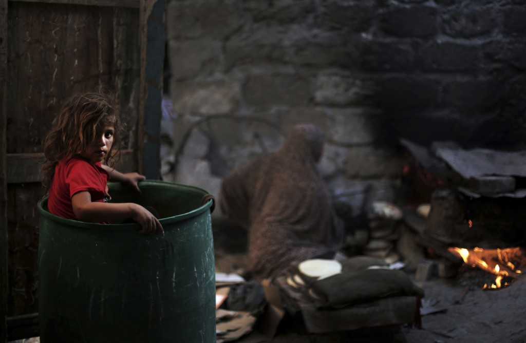 FILE - In this June 20, 2016 file photo, a Palestinian girl plays in a barrel as her mother bakes bread for a Ramadan dinner at their house in el-Zoho