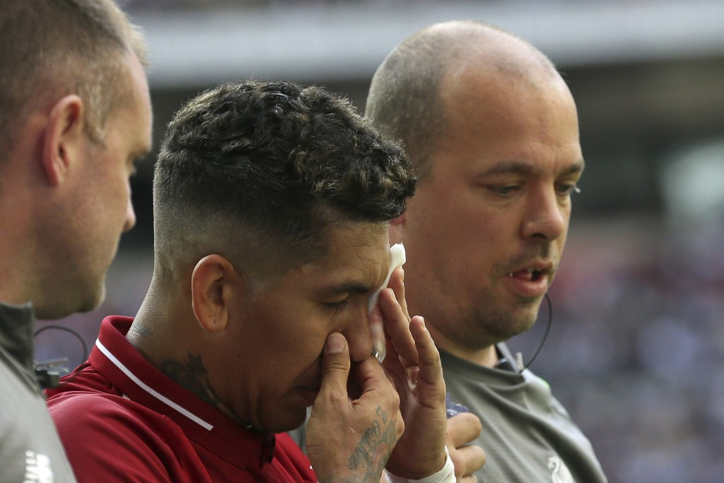 Liverpool's Roberto Firmino, holds a patch over his eye after he received a treatment during the English Premier League soccer match between Tottenham