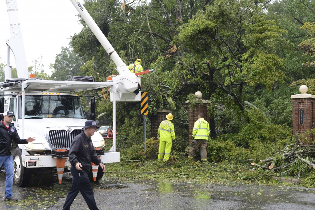 Rains from Hurricane Florence fall as crews remove tree limbs from a power line on Herritage Street Friday, Sept. 14, 2018, in Kinston, N.C. (Janet S.