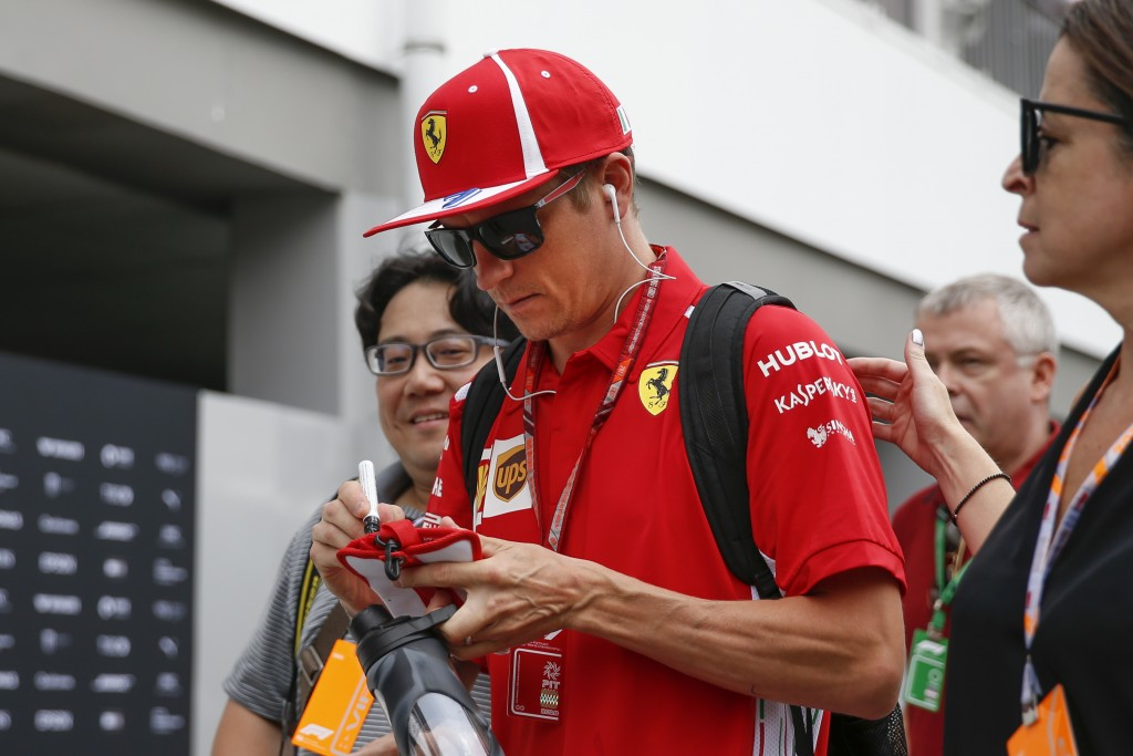 Ferrari driver Kimi Raikkonen of Finland, center, sign autographs as he arrives at the Marina Bay City Circuit ahead of the Singapore Formula One Gran...