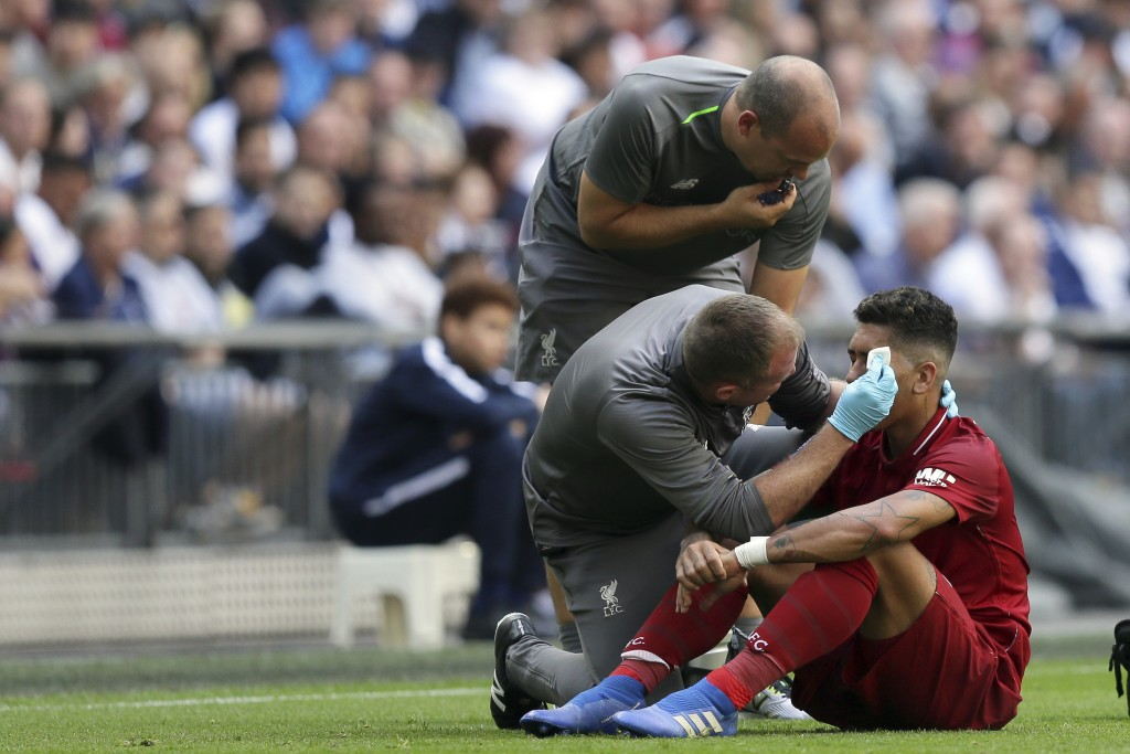 Liverpool's Roberto Firmino, receives a treatment during the English Premier League soccer match between Tottenham Hotspur and Liverpool at Wembley St