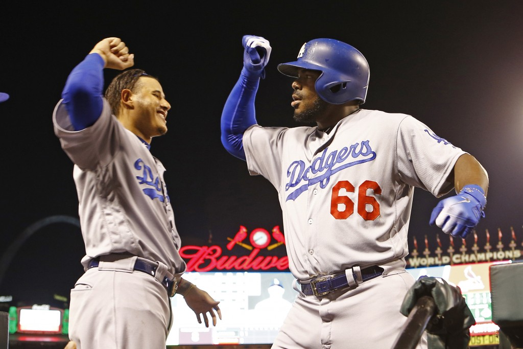 Los Angeles Dodgers right fielder Yasiel Puig, right, is congratulated by teammate Manny Machado after hitting a home run during the first inning of a