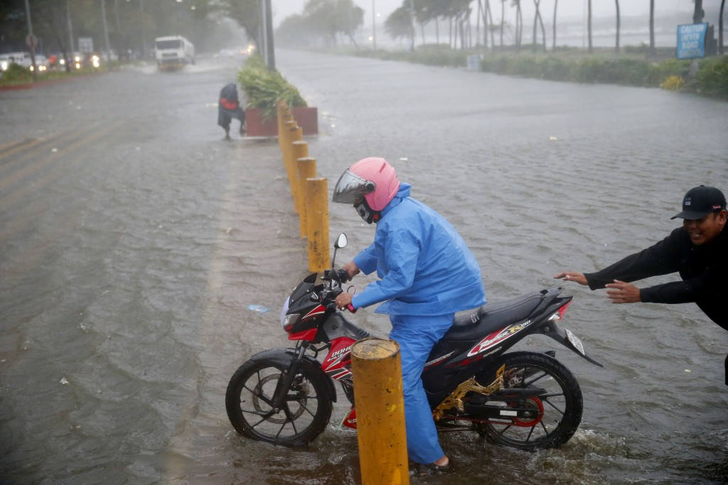 A motorist tries to avoid a flooded Manila street at the onslaught of Typhoon Mangkhut which barreled into northeastern Philippines before dawn Saturd