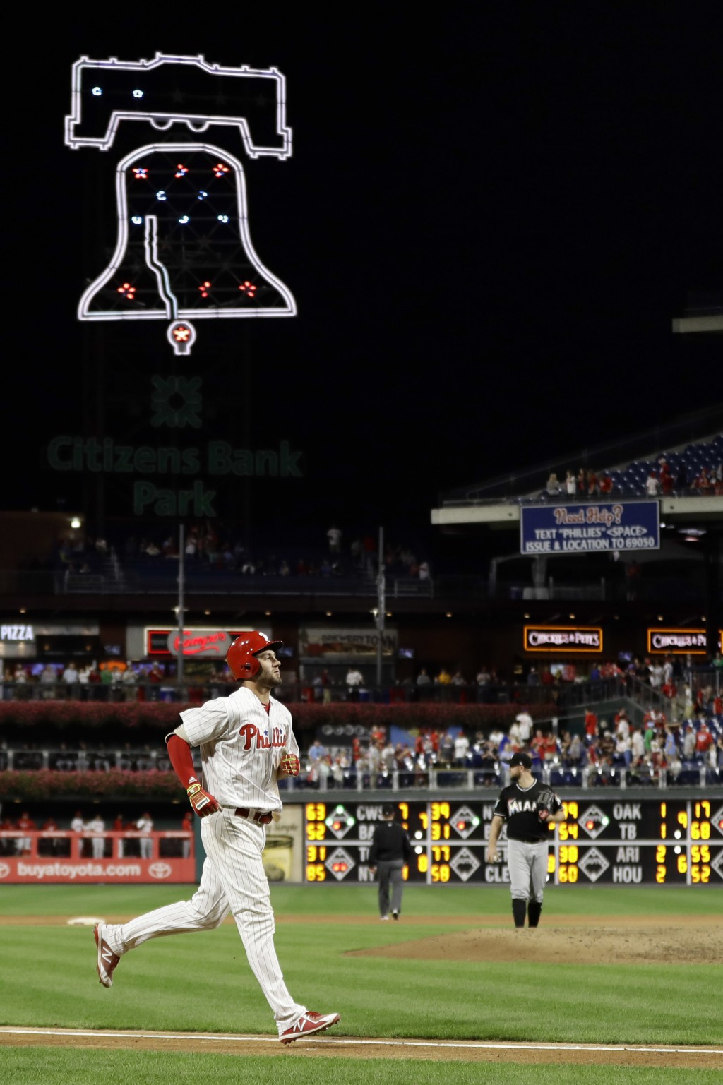 Philadelphia Phillies' Mitch Walding, left, rounds the bases after hitting a two-run home run off Miami Marlins relief pitcher Bryan Holaday during th