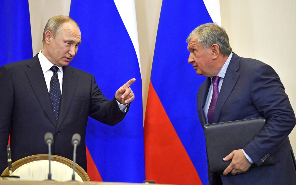 FILE In this file photo taken on Wednesday, May 12, 2018, Russian President Vladimir Putin, left, speaks with Igor Sechin, CEO of Russian oil giant Ro...